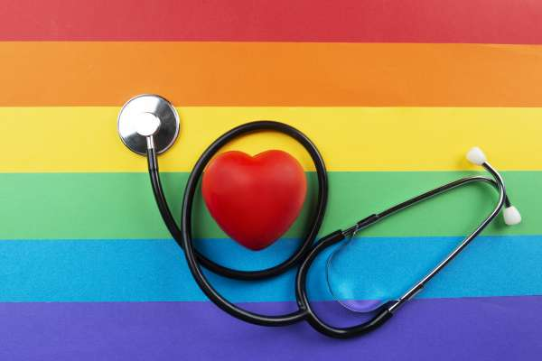 Stethoscope and red heart shape on stripped background made of rainbow flag colors symbolizing LGBT movement.